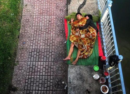 Hạnh phúc giản đơn của cặp vợ chồng vô gia cư ôm nhau ngủ dưới chân cầu ở Sài Gòn