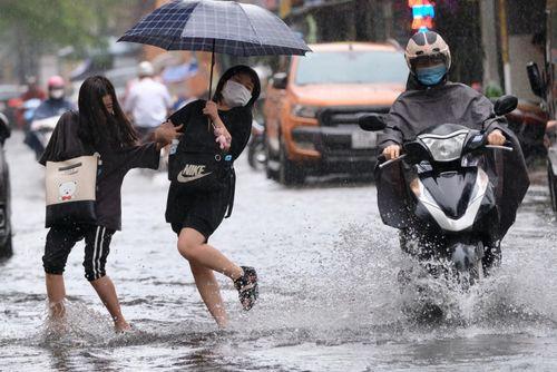 Nữ sinh nhảy tránh nước bắn trong cơn mưa lớn